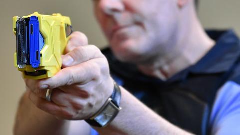 Ein Polizist testet einen Elektroschocker.