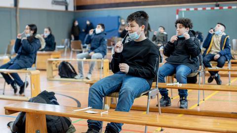 Schüler und Schülerinnen testen sich in der Sporthalle selbst auf das Coronavirus.