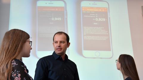 Lehrer Peter Bach, zugleich Medienbeauftragter der Marienschule, diskutiert mit Schülerinnen über eine Physik-Aufgabe. Im Hintergrund sind mit Handys aufgenommene Messwerte zu sehen, die eine Dokumenten-Kamera überträgt.