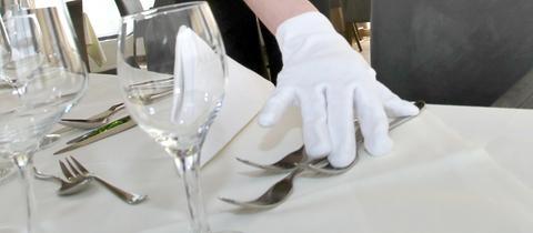 Wei behandschuhte Hände legen silbernes Besteck auf