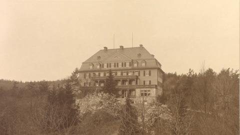Schwarz-Weiß-Aufnahme eines mehrgeschossigen Hauses inmitten der Natur