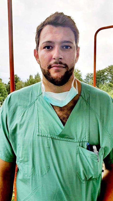 Mann gekleidet in grüner Krankenhaus-Kleidung.