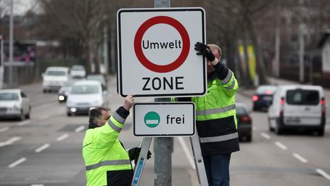 Ein Schild mit der Aufschrift Umwelt-Zone wird aufgehängt.