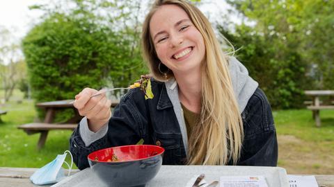 Studentin Johanna Becker auf einer wiedereröffneten Terrasse der Mensa der Uni Gießen