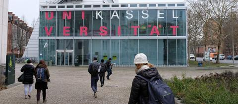 Studenten laufen auf ein Gebäude der Universität Kassel zu
