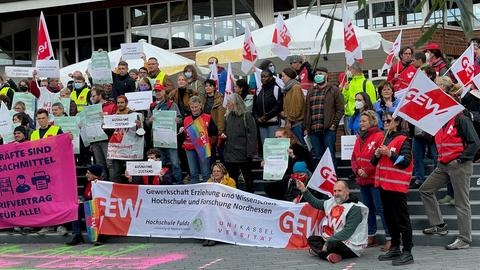 Protest vor der Uni Kassel mit einem Plakat für Entfristung von Verträgen