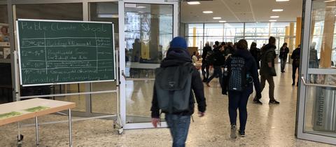 """Der Stundenplan für die """"Public Climate School"""" ist im Audimax der Marburger Uni ausgestellt."""