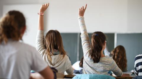 Zwei Mädchen melden sich im Unterricht.