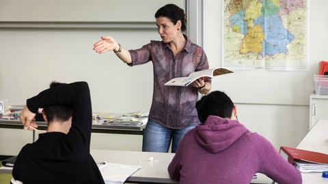 Eine Lehrerin vor einer Schulklasse mit Migranten