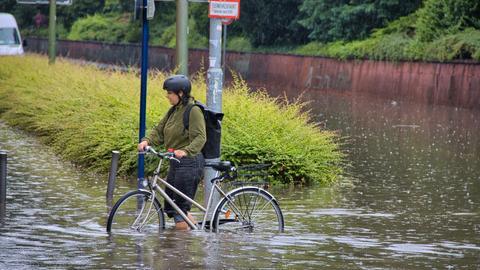Eine Frau schiebt ihr Fahrrad durch kniehohes Wasser. Neben ihr ein Straßenschild. Sie trägt einen Helm und Rucksack.