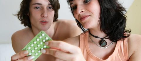 Junges Paar mit der Antibabypille in der Hand