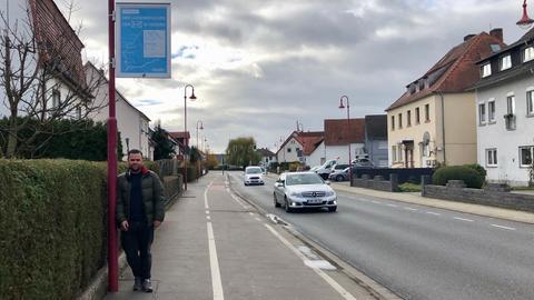 Mann lehnt an Straßenlaterne mit einem Plakat, dass die A49 bewirbt