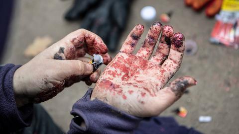 Mit Bastelglitter verklebte Hände erschweren die Identifizierung von Waldbesetzern