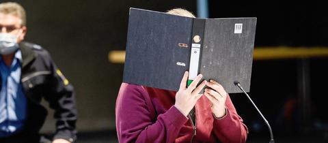 Der Angeklagte sitzt an einem Tisch mit Mikrofon in der provisorischen Gerichtshalle und hält sich einen Ordner vor das Gesicht. Er trägt eine dunkelrote Sweatshirt-Jacke.. Im Hintergrund ist ein Sicherheitsbeamter zu sehen.
