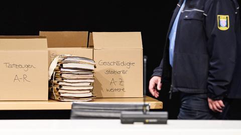 """Kartons mit Akten auf einem Tisch in der provisorisch eingerichteten """"Gerichtshalle""""."""