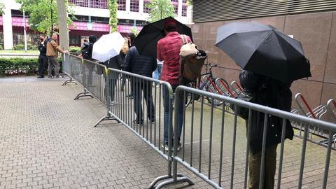 Interessierte Zuschauer warten geduldig vor dem Gerichtsgebäude.