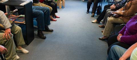 Viele Patienten sitzen in einem Wartezimmer einer Arztpraxis.