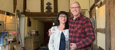 Heike Gunson und ihr Mann David stehen in einem Raum ihres Fachwerkhauses. Im Hintergrund sind Kisten und Werkzeuge zu sehen.