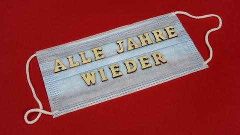 """Auf einer Mundschutzmaske liegt der Schriftzug """"Alle Jahre wieder""""."""