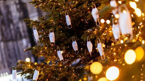 Mehrere Einwegmasken hängen an einem beleuchteten Weihnachtsbaum