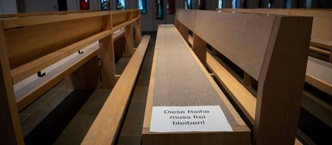 """Foto aus einer Kirche. Auf eine Bank ist ein Zettel mit der Aufschrift """"Diese Reihe muss frei bleiben"""" geklebt."""