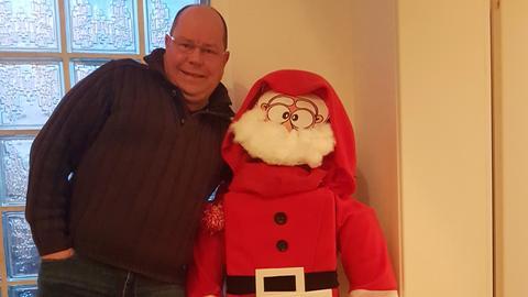 Oliver Hess steht neben einem Weihnachtsmann
