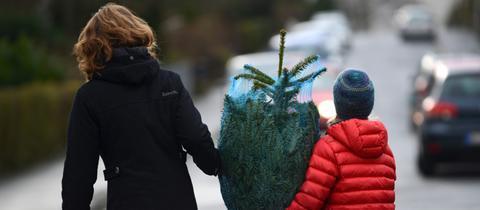 Mutter und Tochter tragen einen gekauften Weihnachtsbaum weg