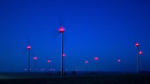 Beleuchtete Windräder bei Nacht