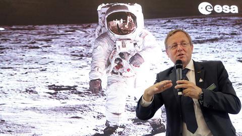 Johann-Dietrich Wörner steht vor dem Foto eines Astronauten.