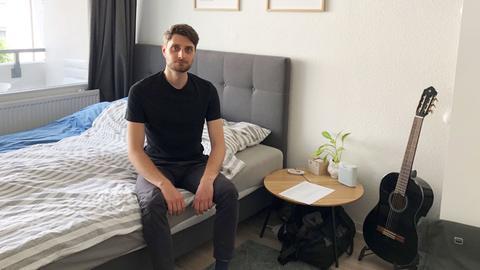 Kevin Sokoll sitzt auf einem Bett in seiner Wohnung. Im Hintergrund sind Bilder an der Wand zu sehen. Neben ihm ein kleines Tischchen und eine Gitarre.