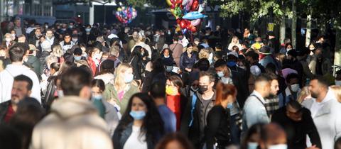 Menschen laufen mit und ohne Maske über die Zeil.