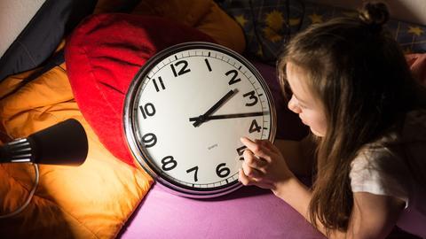 Ein Mädchen stellt die Uhr von 3 auf 2 Uhr zurück.