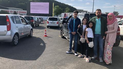 Familie steht am Auto auf einem vollen Parkplatz mit einer Leinwand