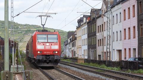 Ein Güterzug fährt in Lorch (Rheingau-Taunus) unmittelbar an Wohnhäusern vorbei.