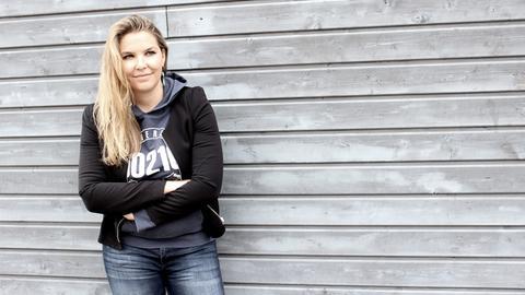 Eine blonde Frau lehnt an einer Wand und lächelt.