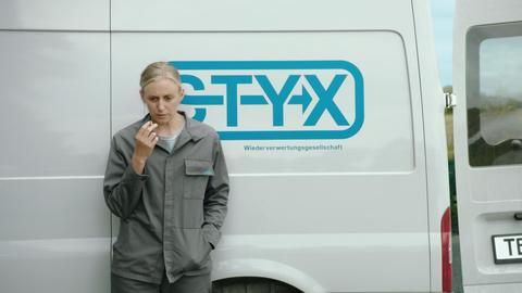 """Rauchende Frau steht im Arbeitsoverall vor einem Kleinlaster mit der Aufschrift """"Styx"""""""