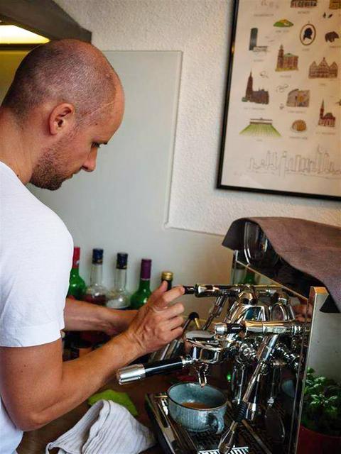 Junger Mann an einer Espresso-Maschine
