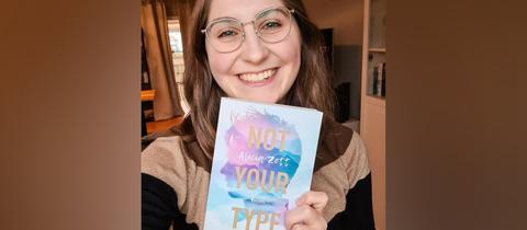 """Alicia Zett (eigentlich Zimmermann) hält ihr Buch """"Not Your Type"""" in die Kamera."""