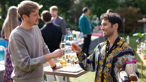 Zwei Männer prosten sich auf einer Gartenparty mit Sekt zu