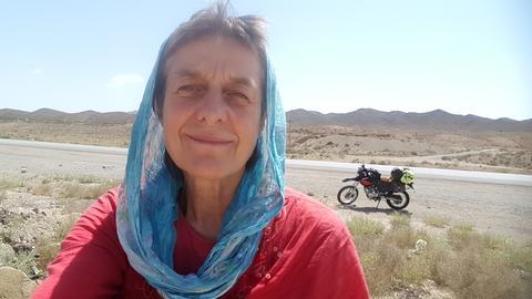Ältere Frau mit Kopftuich in der Wüste, im Hintergrund ein Motorrad.
