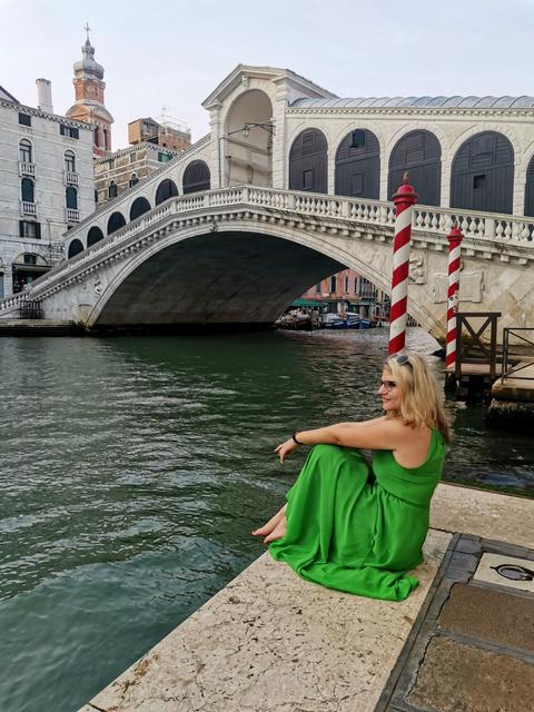 Junge Frau in grünem Kleid an einer Brücke in Venedig