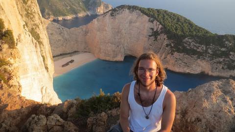 Junger Mann in Unterhemd vor einer Felsenküste