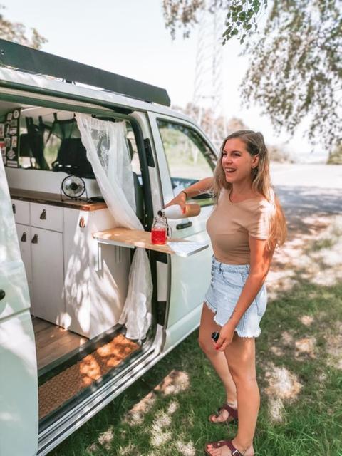 Junge Frau schenkt sich neben ihrem ausgebauten Van ein Glas ein.