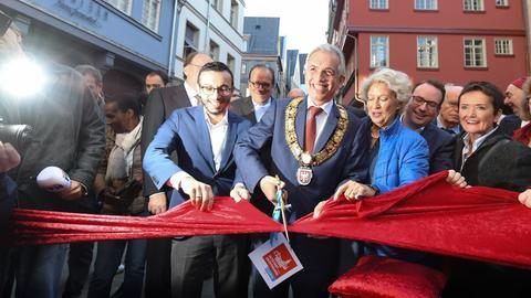 Frankfurts OB Feldmann (SPD) schneidet im Beisein seiner Amtsvorgängerin Roth (CDU, 3.v.r.) bei der offiziellen Eröffnung der Altstadt ein Band durch.