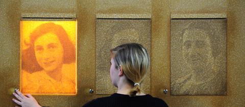 Eine Frau bedient der Bildungsstätte Anne Frank eine Lampe hinter einem Portrait von Anne Frank.