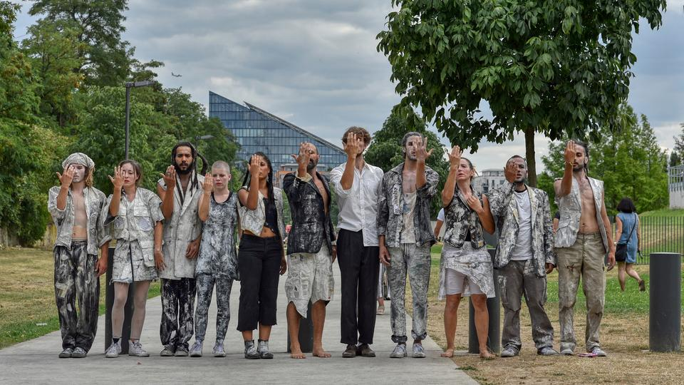 Elf Leute mit abgerissener Kleidung und weiß geschminkten Gesichtern in einer Reihe