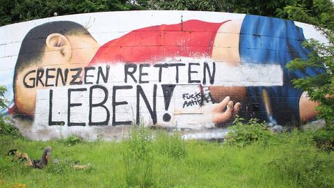 """Das Aylan-Gemälde in Frankfurt wurde mit der Parole """"Grenzen retten Leben"""" überschrieben."""