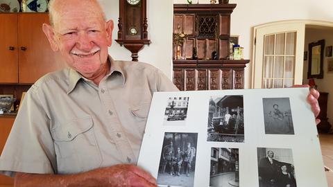 Baldur Schreiner hält einen Bilderrahmen mit Fotos aus der Altstadt in der Hand.