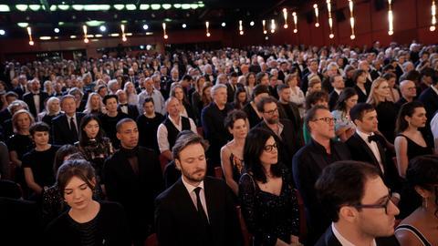Das Berlinale-Publikum steht während einer Schweigeminute für die Opfer des Anschlages in Hanau bei der feierlichen Eröffnung der Internationalen Filmfestspiele.