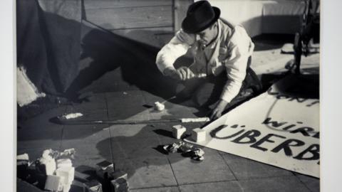 Ein Foto zeigt Josef Beuys wie er ein Plakat malt.
